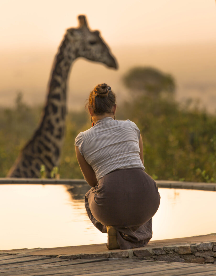 Lady and giraffe by pool
